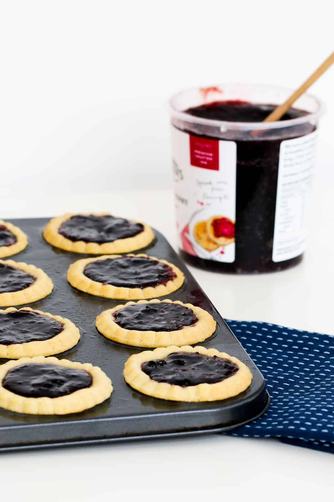 A patty pan tin filled with pastry and jam.