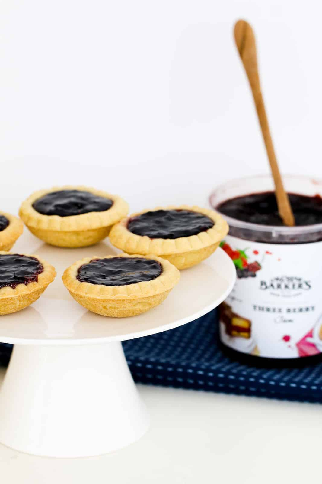 A cake stand with jam tarts on it and a jar of jam in the background.