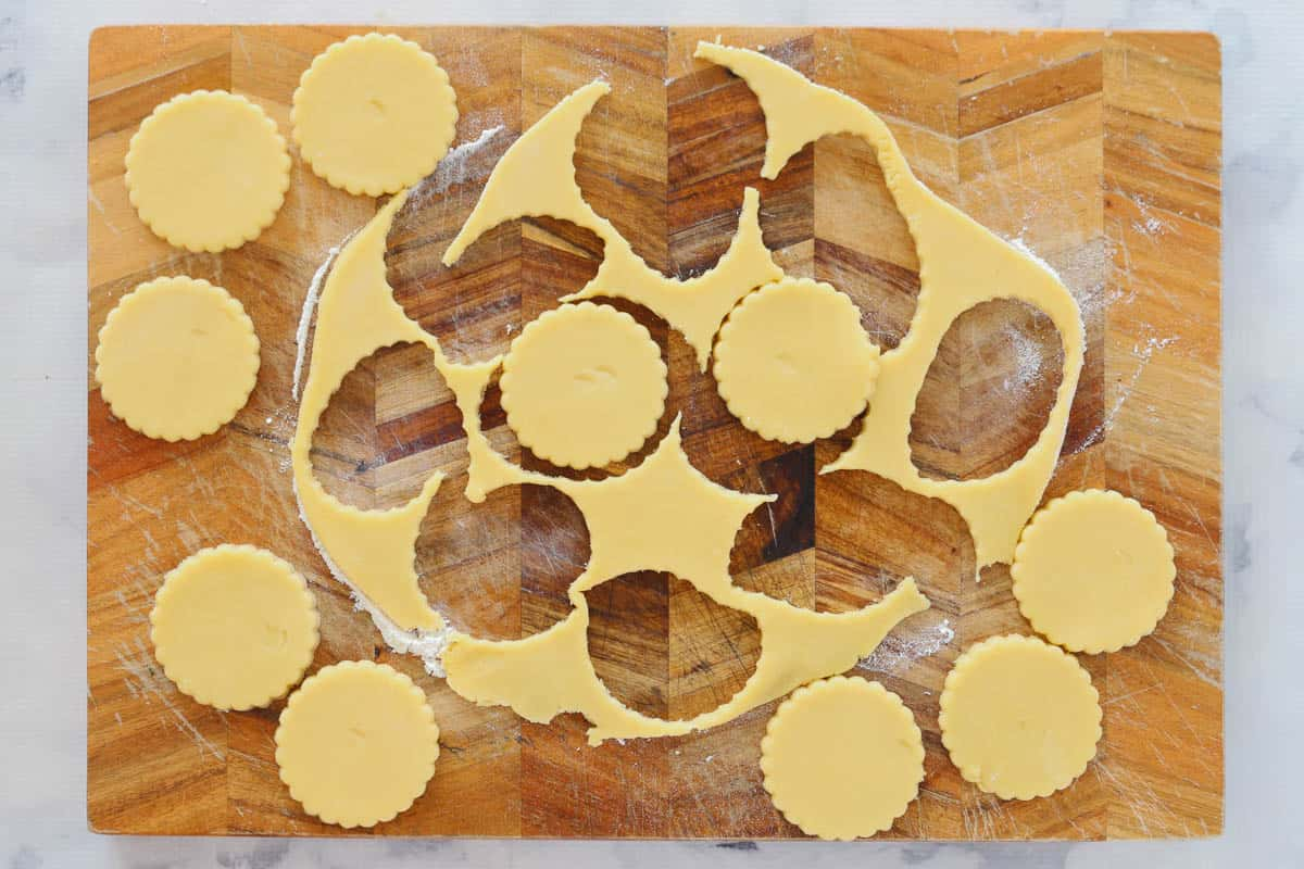 Pastry circles being cut out on a floured wooden board.