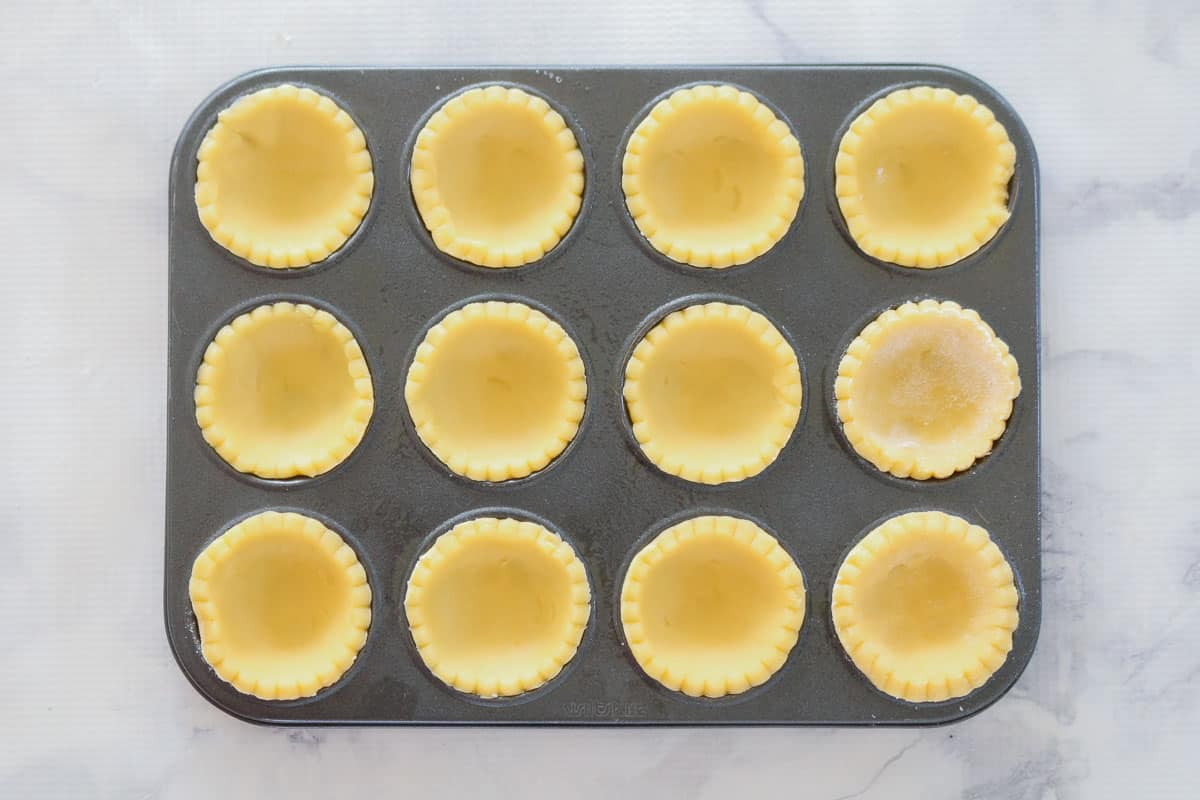 Patty pan tin holes filled with circles of sweet pastry.