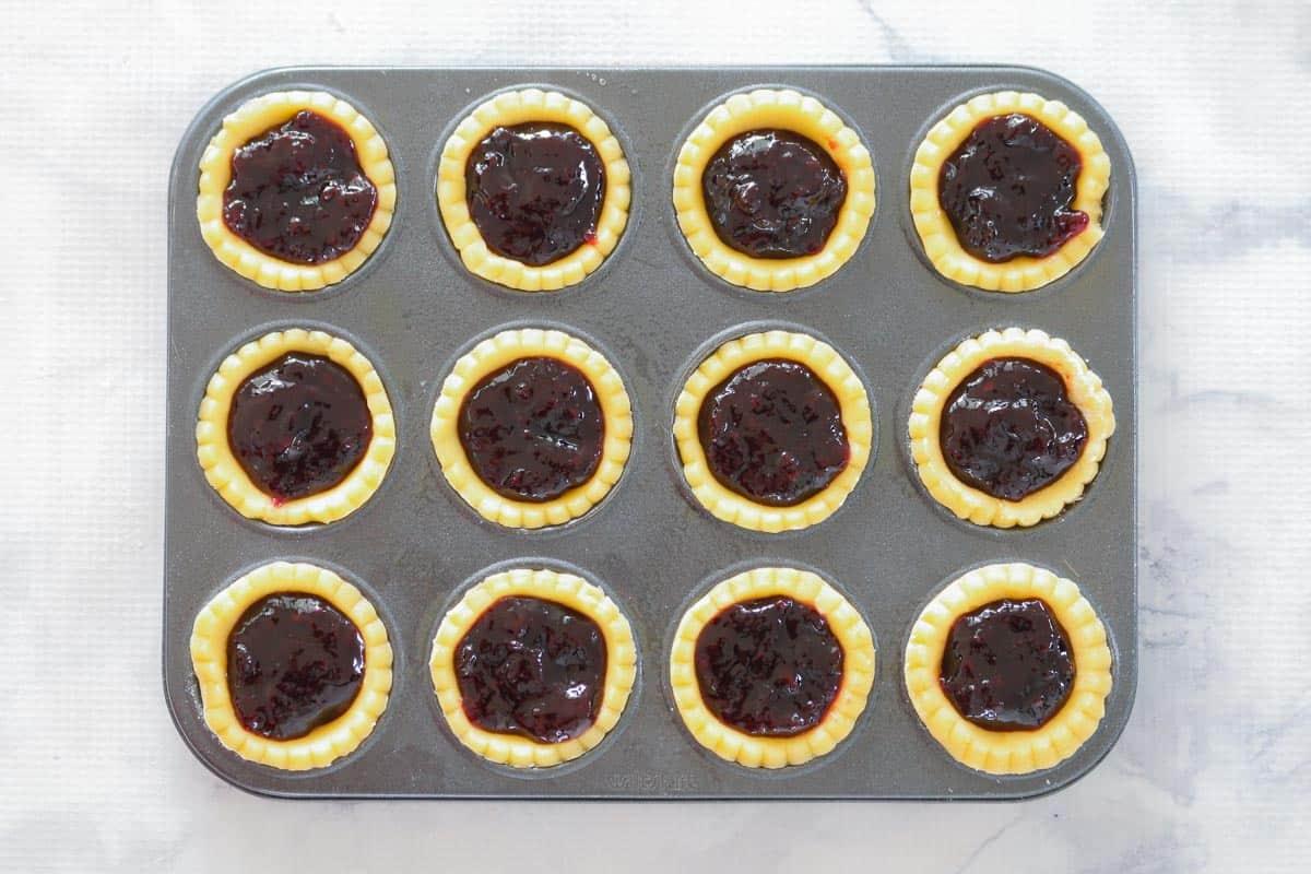 Mini jam tarts in patty pan tins.