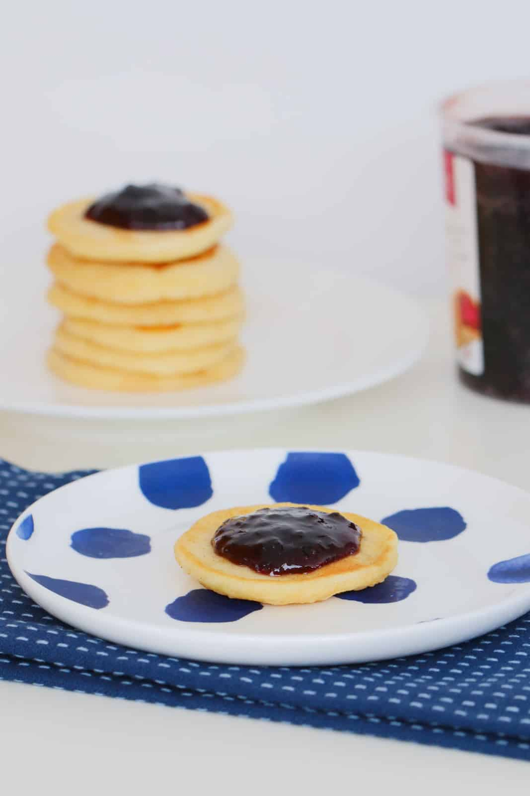 A jam topped pikelet on a blue and white plate.