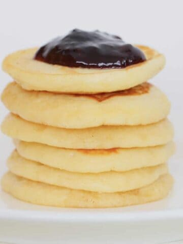 A stack of pikelets on a white plate.