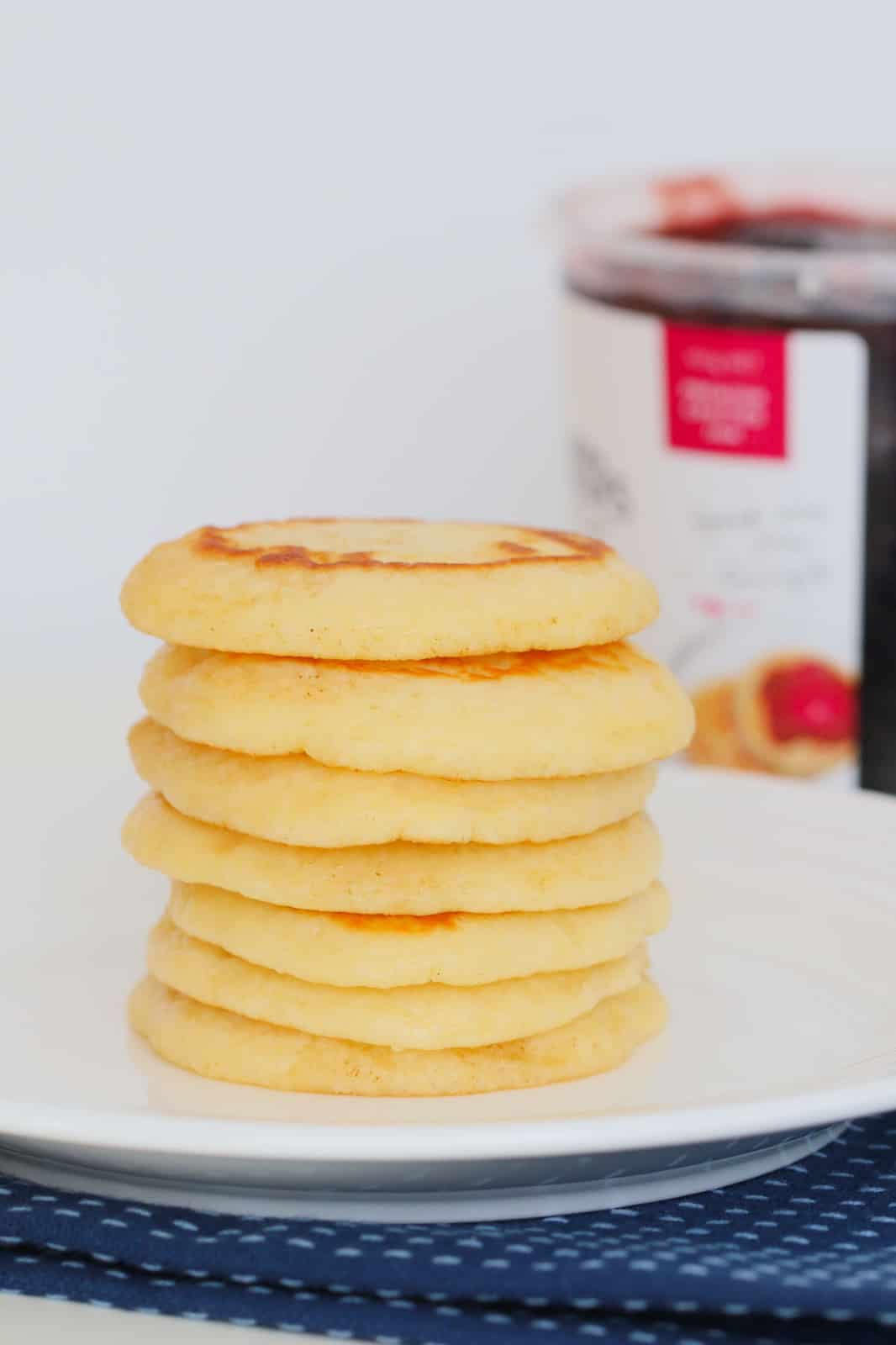 A stack of pikelets on a white plate with a jar of jam in the background..