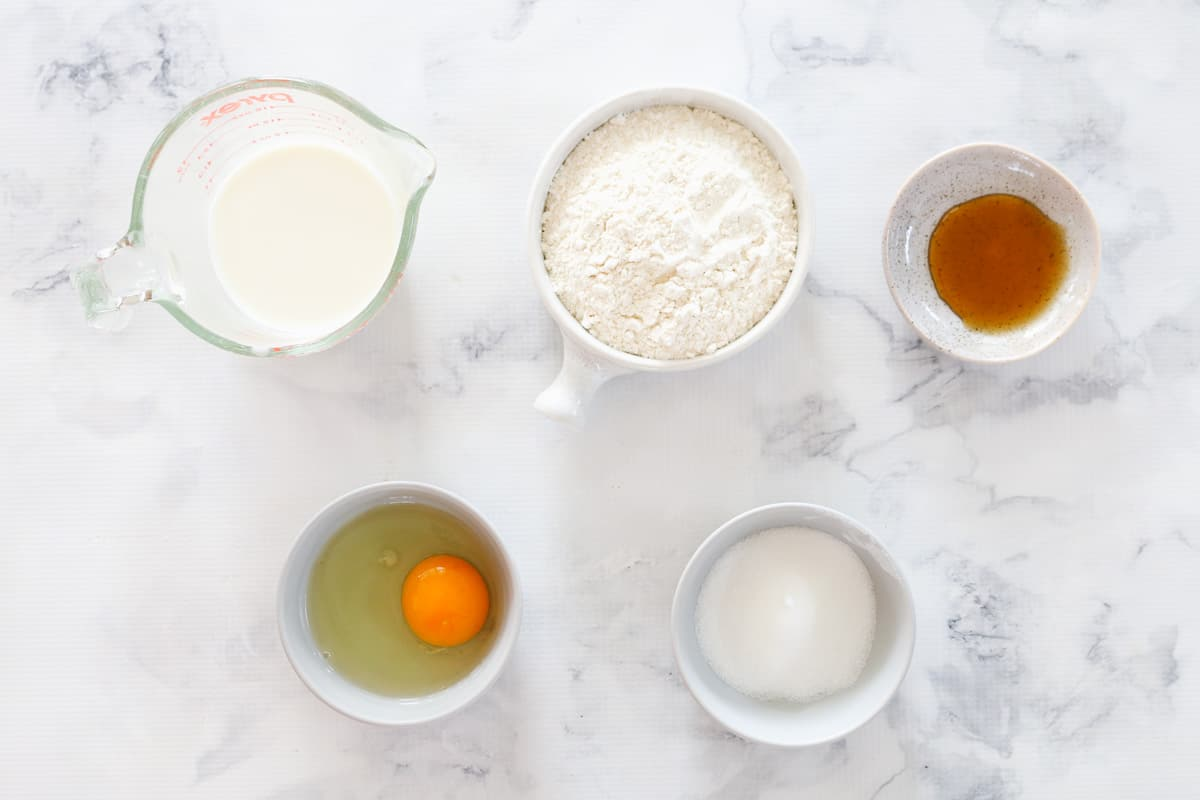 The ingredients to make pikelets in individual bowls on a bench top.