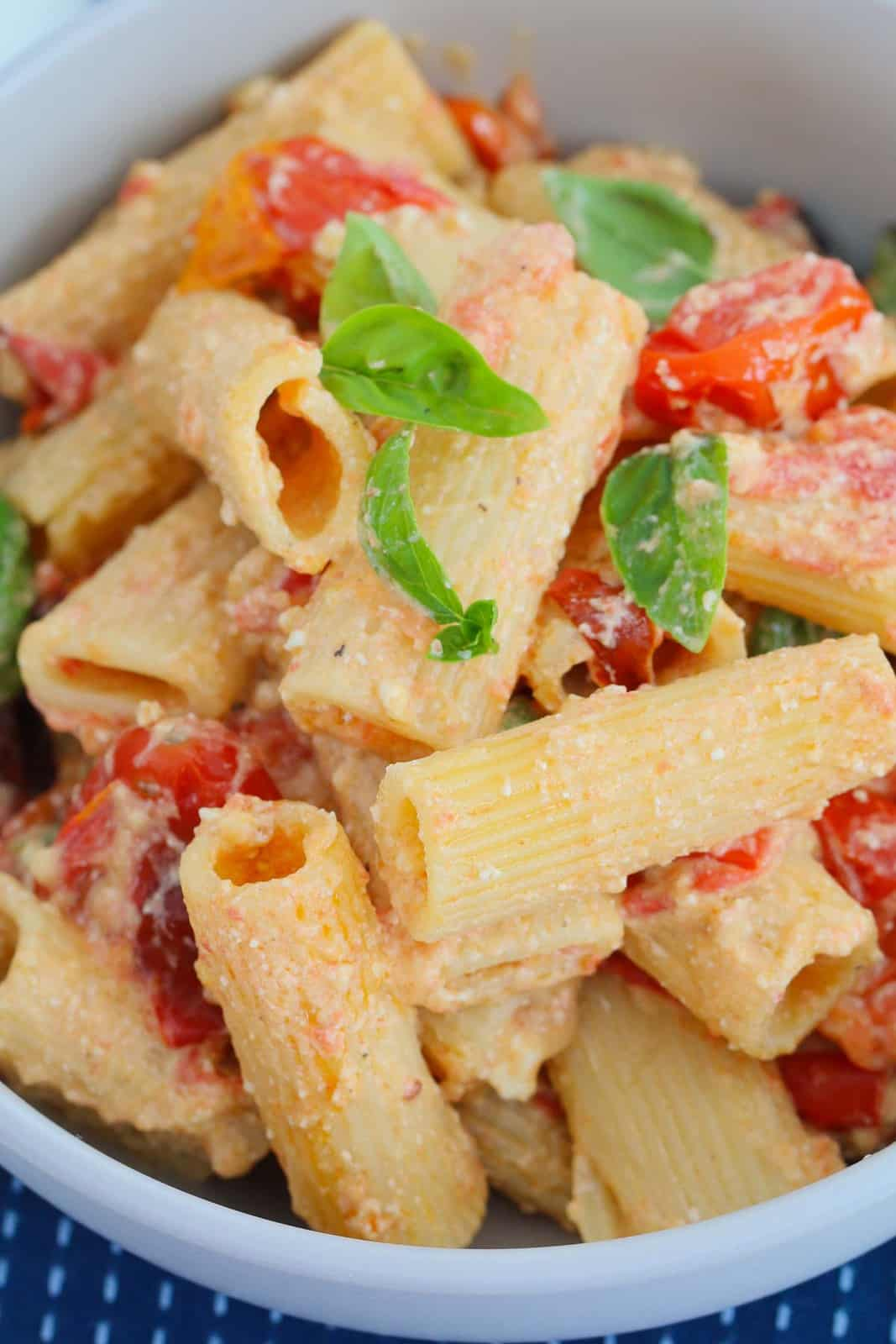 A bowl of rigatoni with basil, tomato and feta.