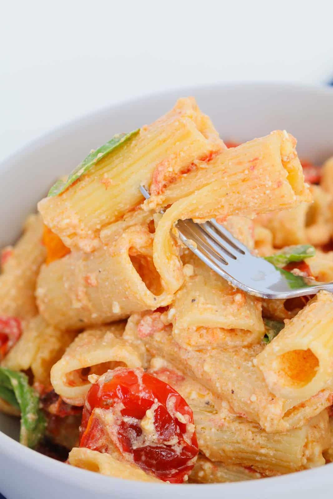 A bowl of Tik Tok tomato & feta pasta with a forkful of pasta.