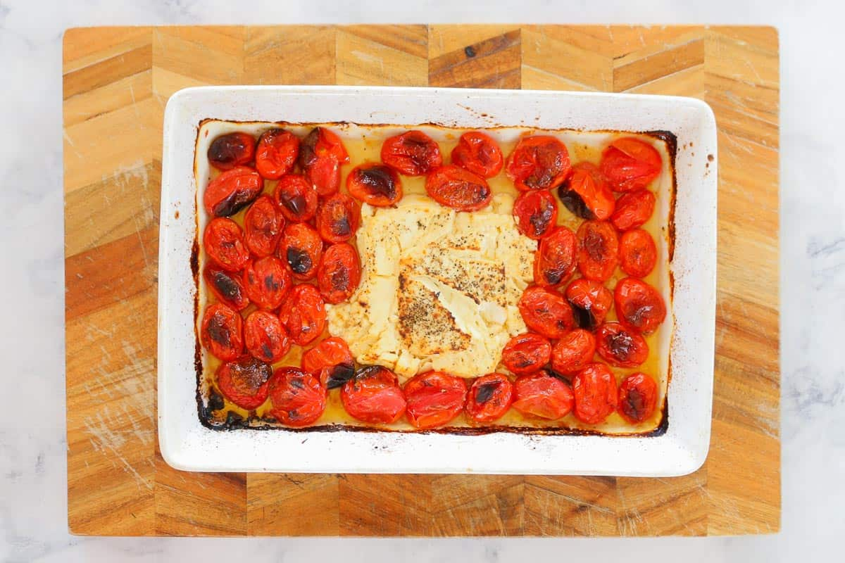 Soft baked feta and charred tomatoes in a baking dish.