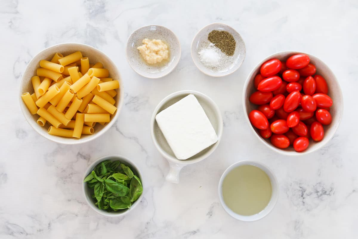 The ingredients for baked feta pasta in individual bowls.