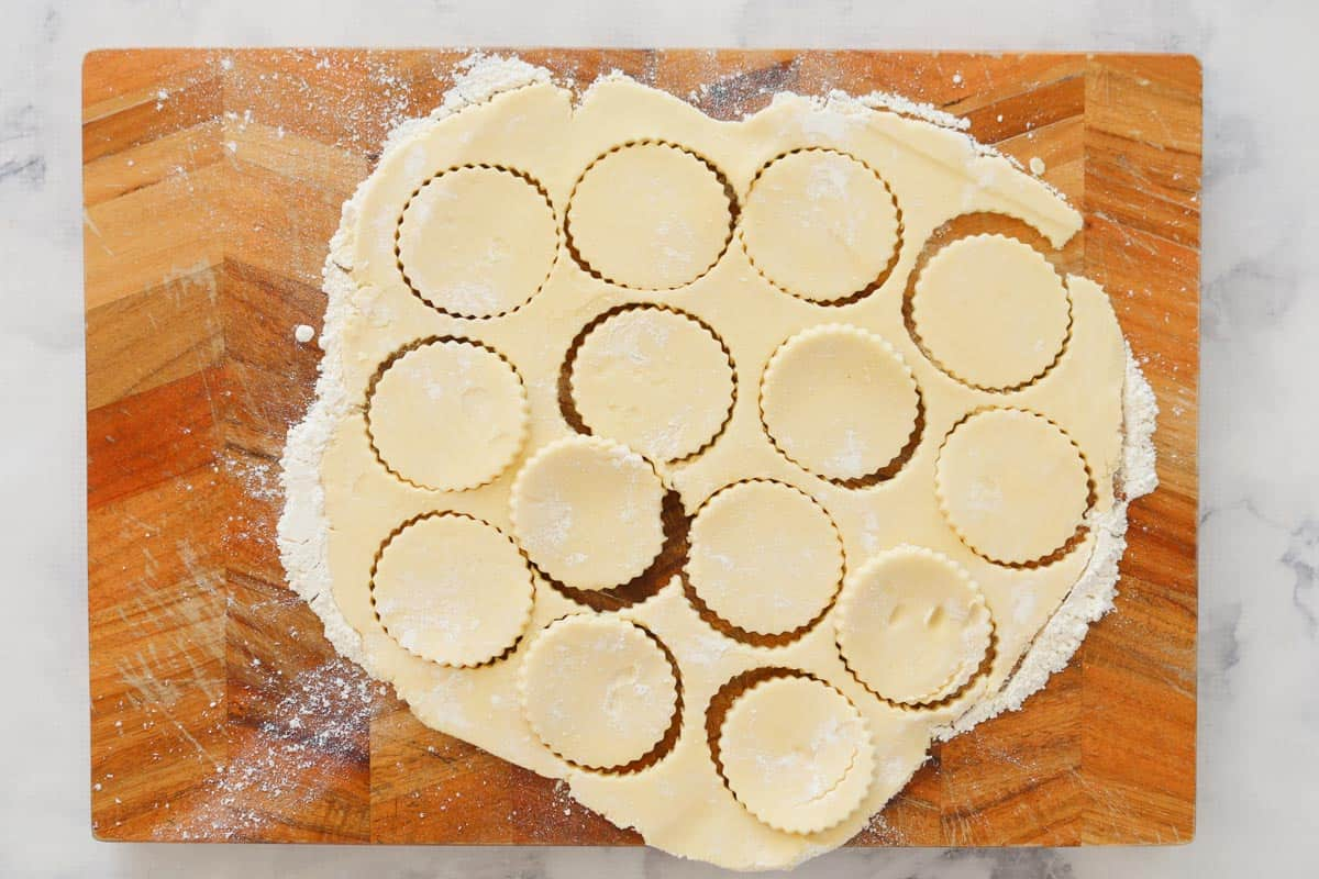 Biscuits cut out of dough on a floured wooden board