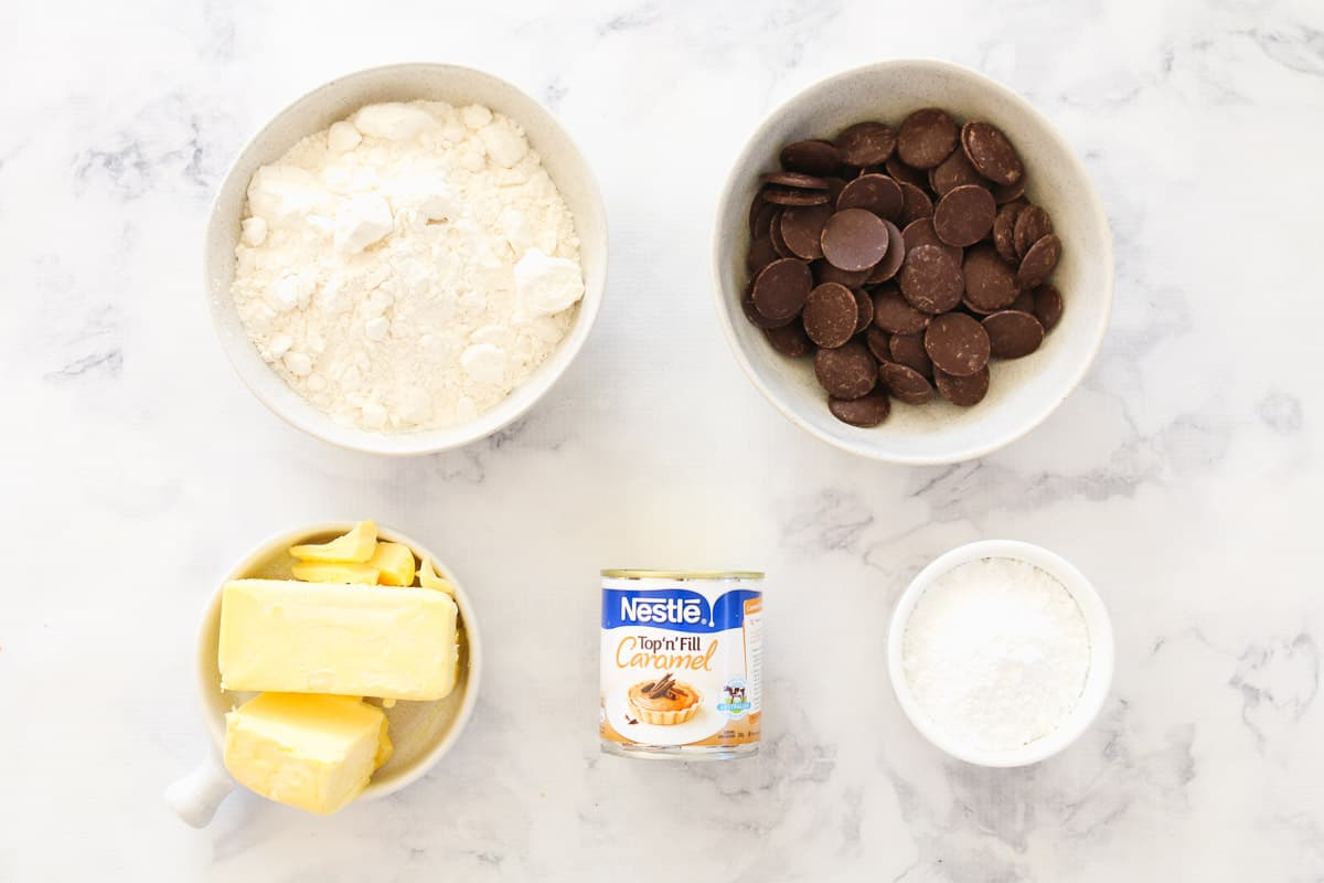 The 5 Ingredients in Twix Cookies on a marble bench top.