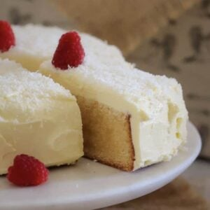 A piece of white chocolate mud cake with frosting and raspberries being removed from an entire cake.