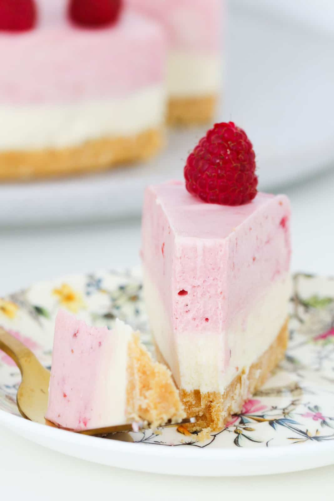 close up shot of cheesecake with white and pink layers garnished with fresh berries
