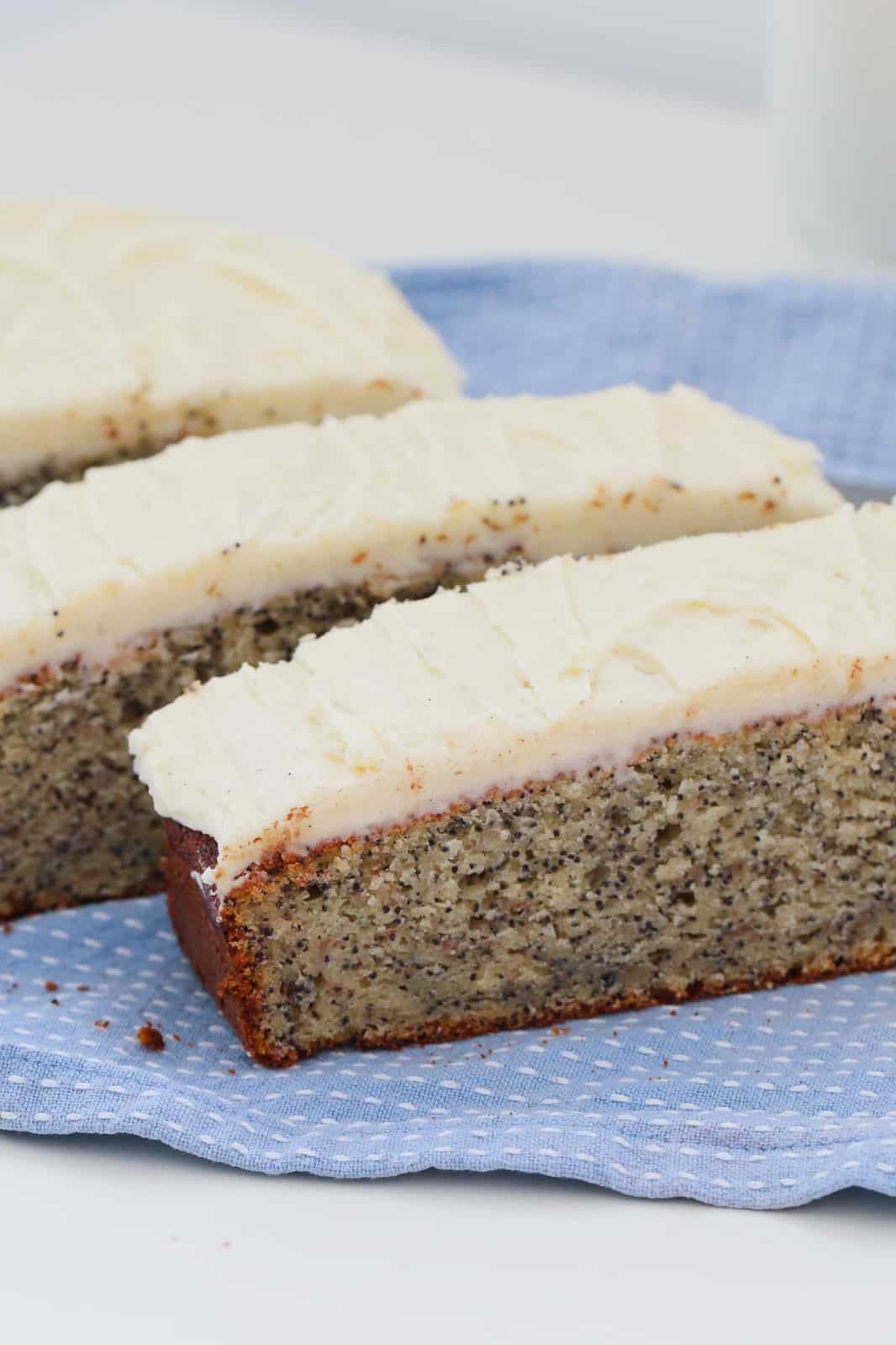 Three long, thick slices of frosted poppyseed cake on a blue and white tea towel on a white counter top..