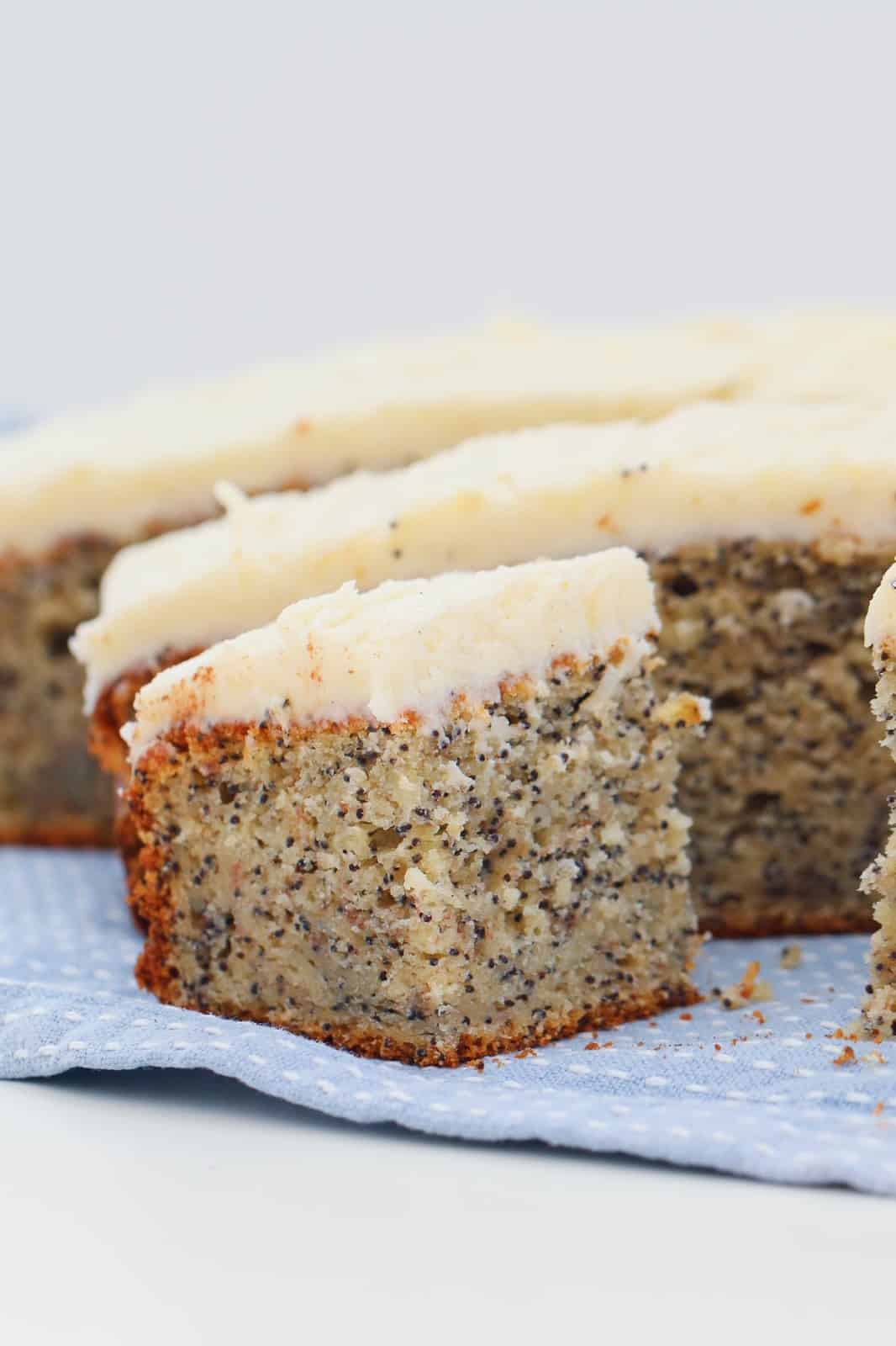 A piece of frosted poppyseed cake on a blue and white tea towel in front of the rest of the sliced cake.
