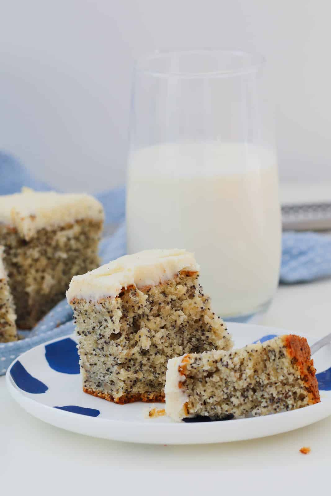 A split piece of frosted poppy seed cake on a white & blue plate, with a glass of milk and more cake on a blue and white towel in the background.
