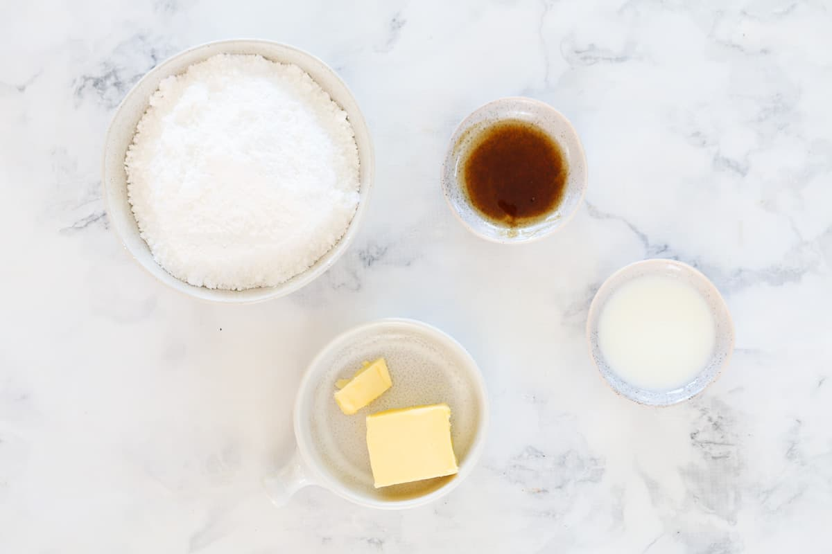 Four bowls with icing mixture, butter, milk and vanilla extract on a marble counter top.