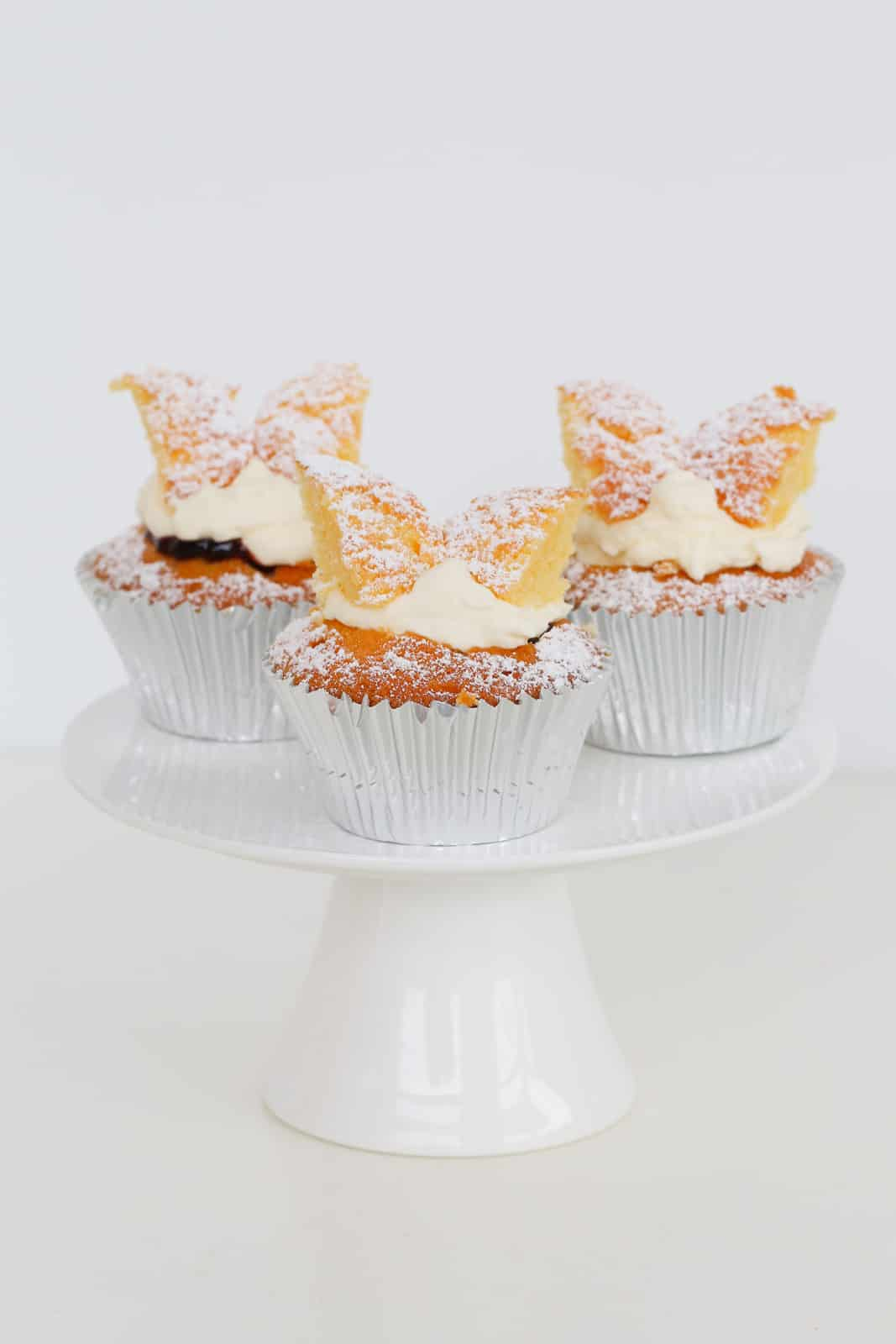 Three butterfly cupcakes with fairy wings and cream on a cake stand.
