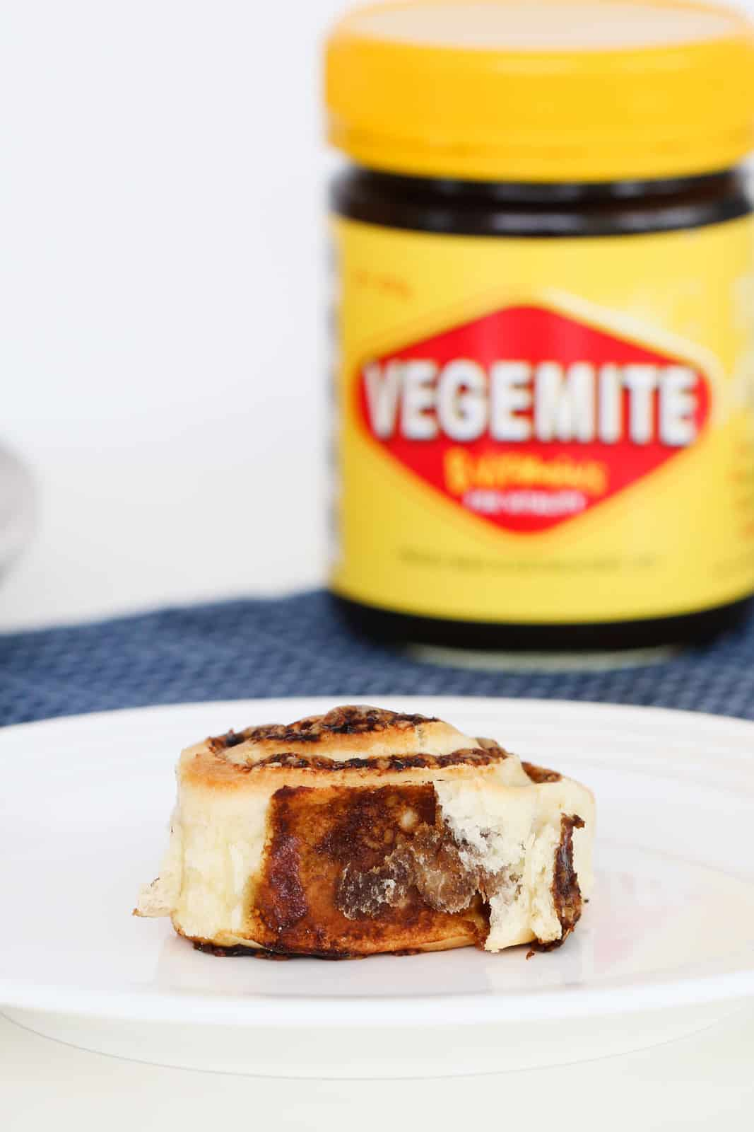A scroll with a cheese and vegemite filling on a white plate in front of a slightly blurred jar of Vegemite