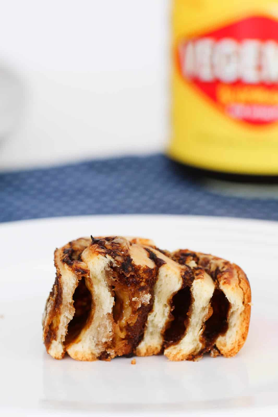 A baked scroll split to reveal the inside of a cheese and Vegemite scroll.