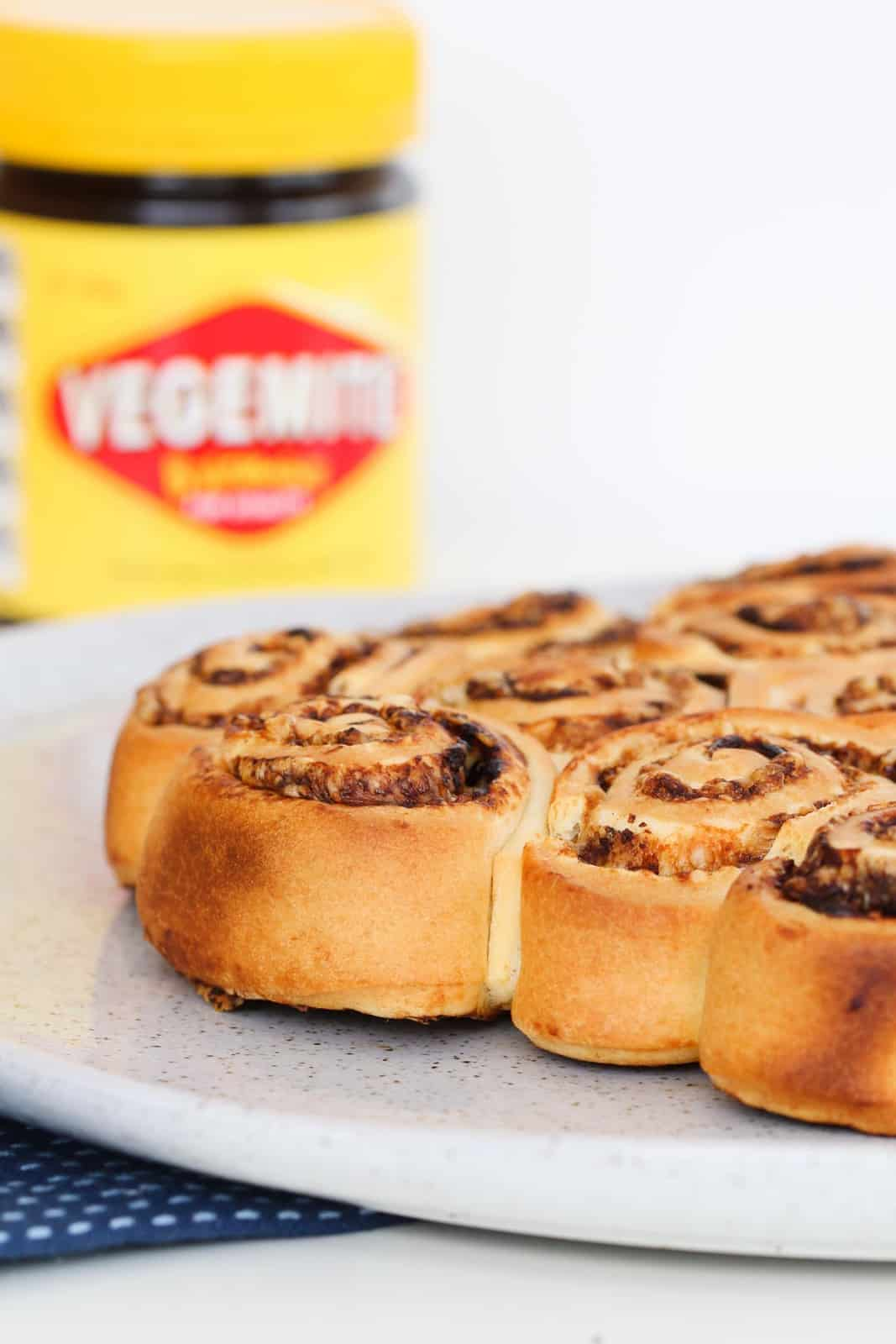 A speckled white plate with cheese and vegemite bread scrolls and a blurred Vegemite jar in the background.