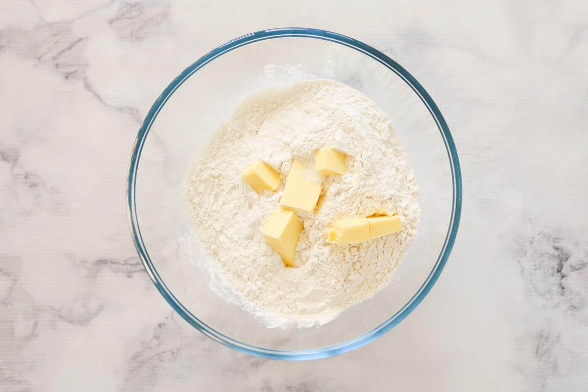 Self-raising flour and butter in a glass bowl.