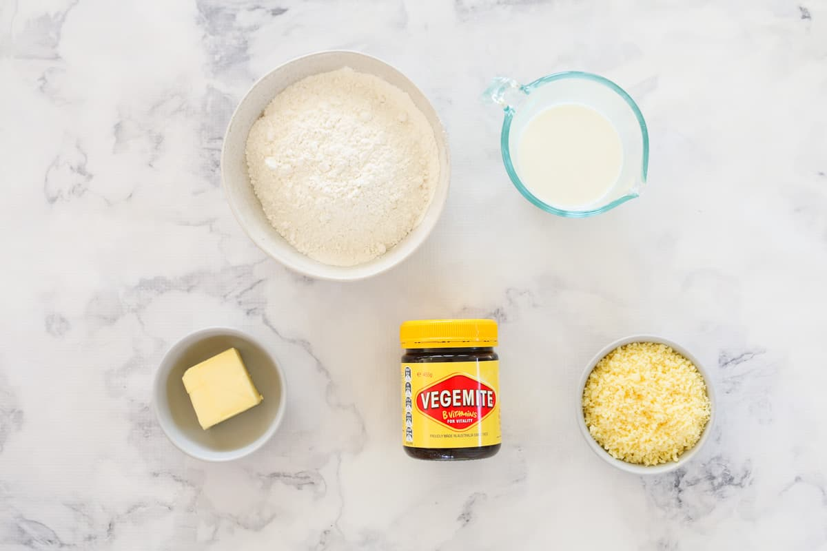 Flour, butter, milk, butter, Vegemite and grated cheese on a marble bench top.