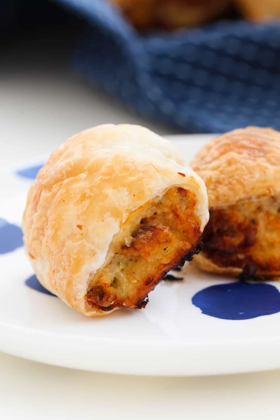 Two golden baked chicken sausage rolls on a blue and white plate.