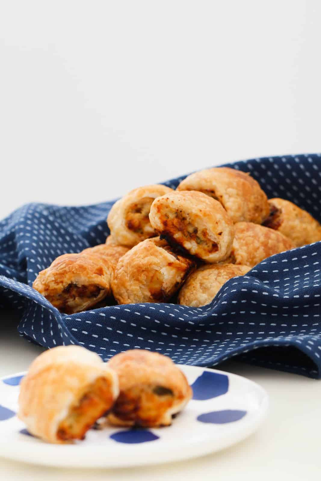 A batch of homemade chicken sausage rolls piled on a blue tea towel, and two served on a plate.