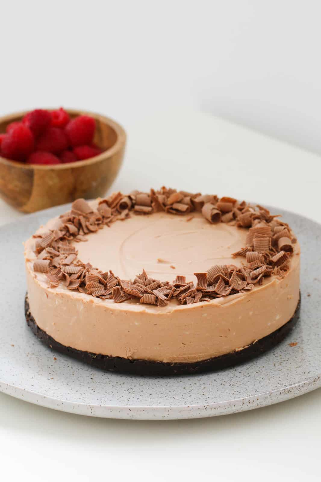 A round chocolate cheesecake with grated chocolate on top, and a bowl of raspberries in the background.