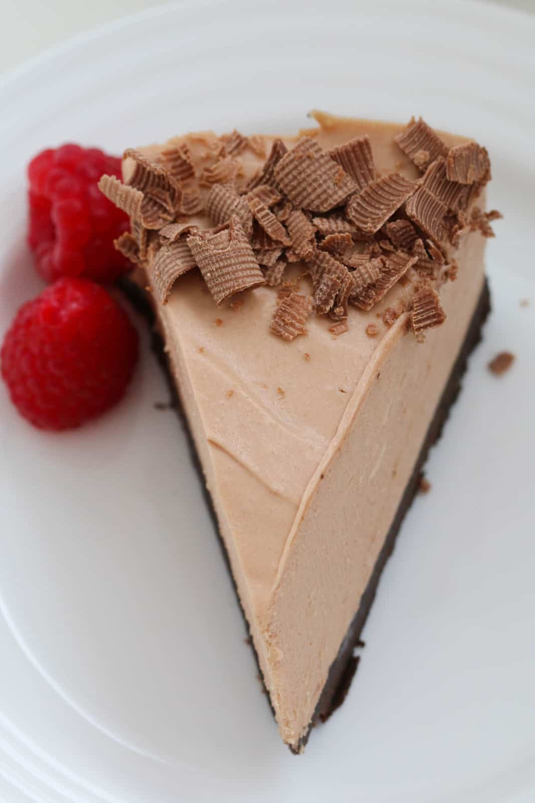 An overhead shot of a serve of cheesecake with chocolate on top and raspberries beside.