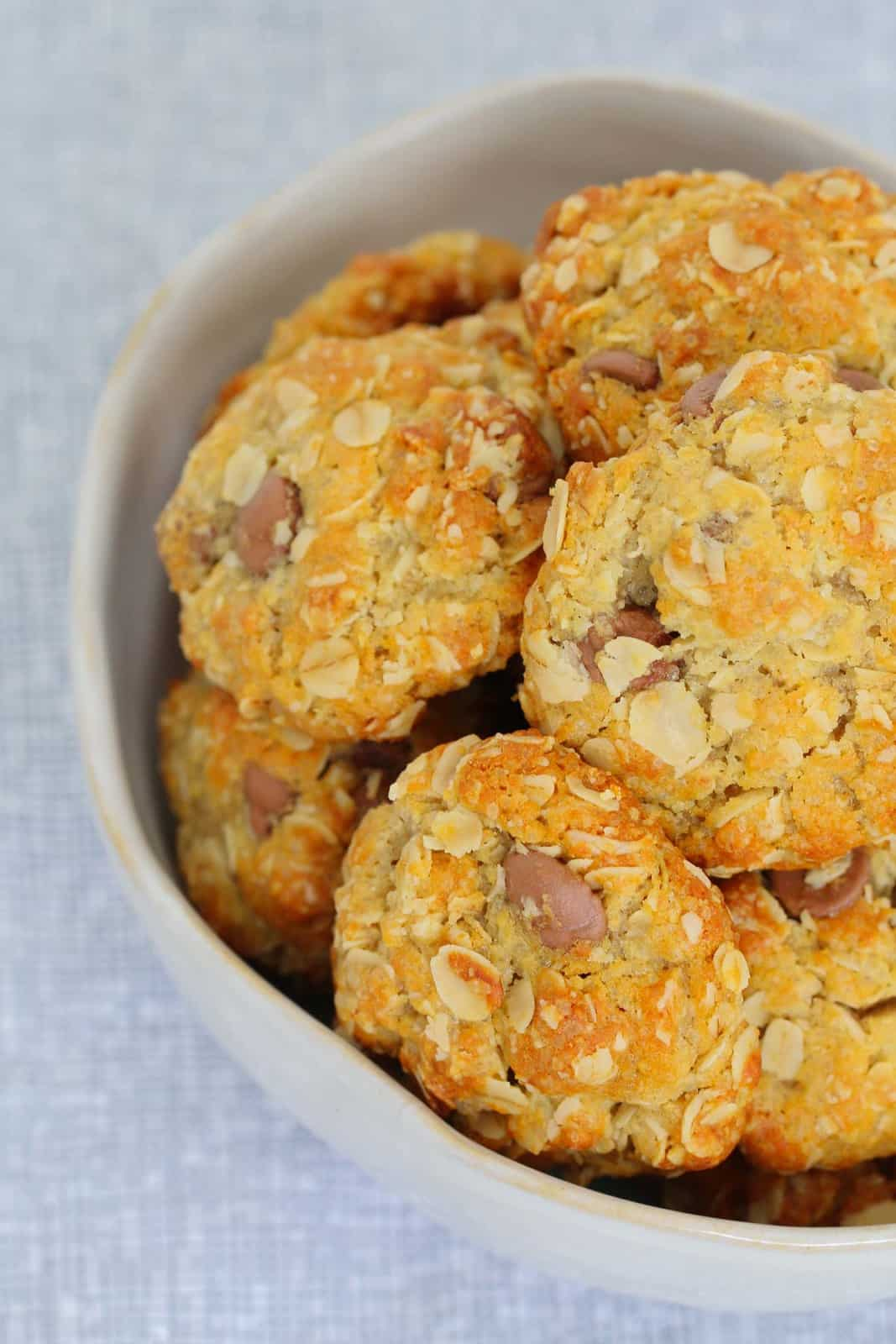 A bowl filled with golden baked oat biscuits made with chocolate chips.