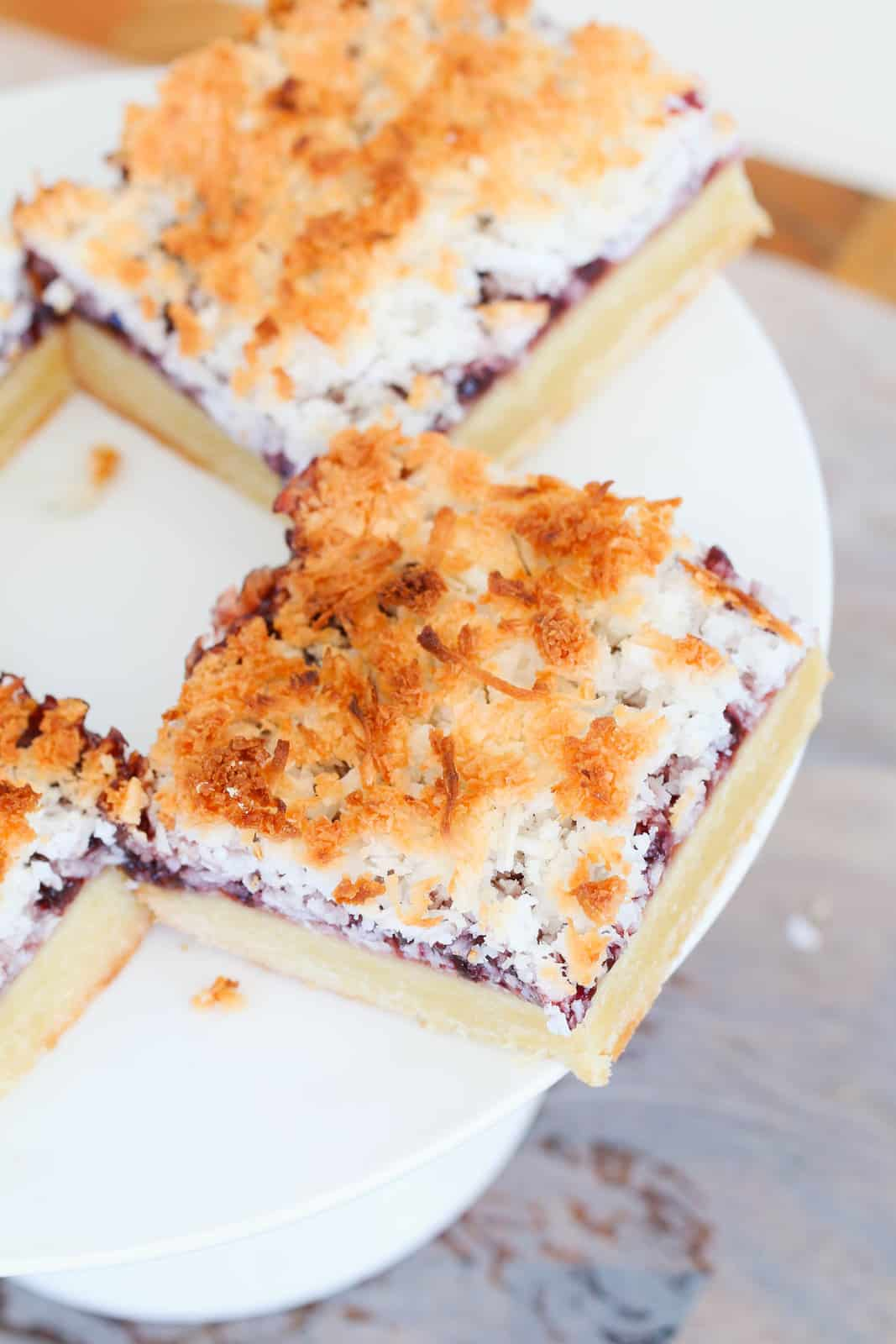 An overhead shot of two squares of Raspberry Coconut Slice on a white cake stand