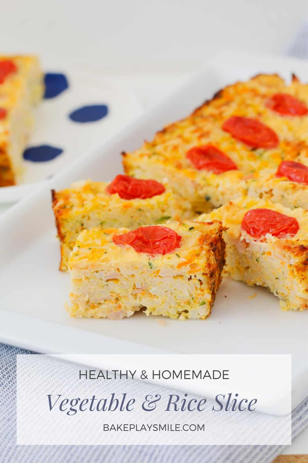 Pieces of a rice & vegetable slice, with cherry tomatoes on top.