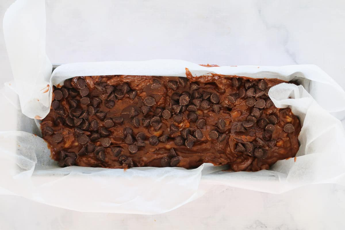 Chocolate banana bread batter in a paper lined loaf tin sprinkled with chocolate chips.
