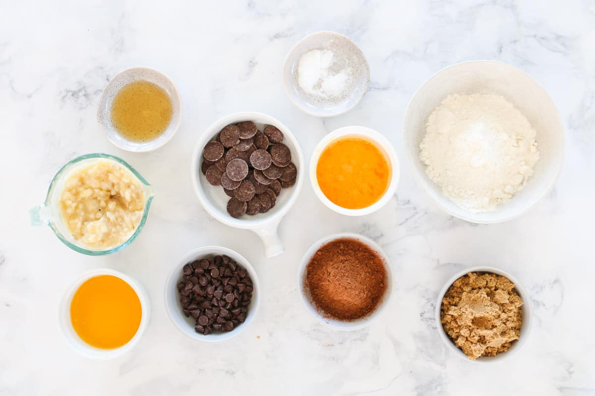 Ingredients for chocolate banana bread measured out into individual bowls on a marble counter top.