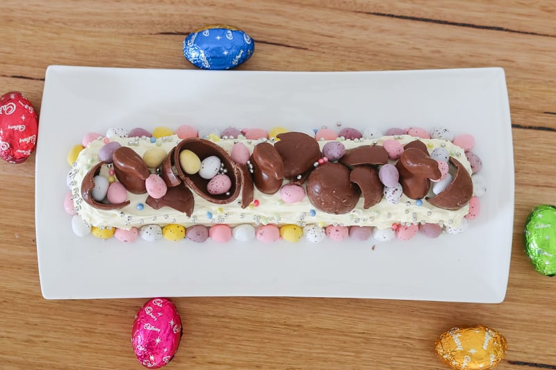 A dessert made with chocolate cookie and cream in a log shape decorated with Easter eggs.
