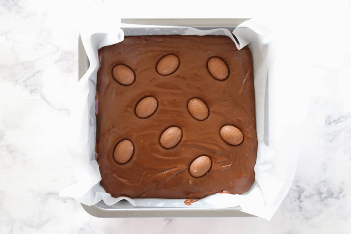 Easter eggs pressed into chocolate fudge in a lined square baking tin.