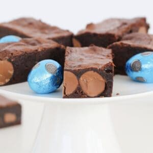 A white cake stand topped with moist brownies filled with Easter eggs,