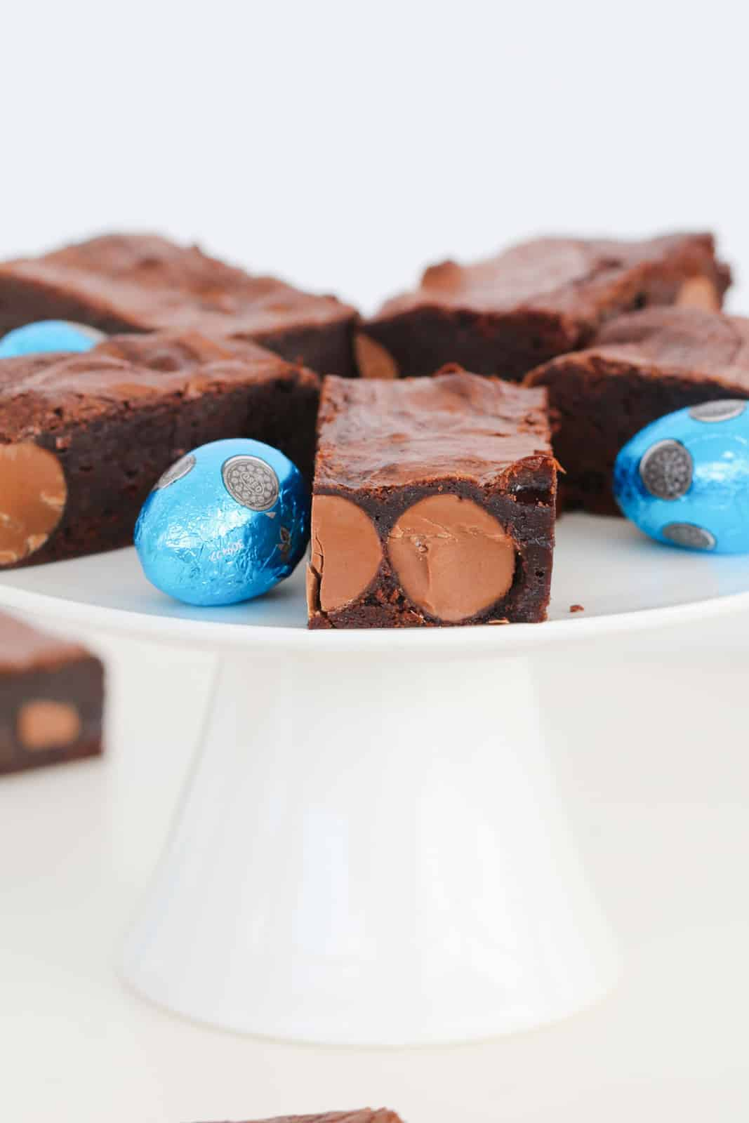 A white cake stand topped with moist brownies filled with Easter eggs, and more wrapped Easter eggs to decorate around brownie pieces.
