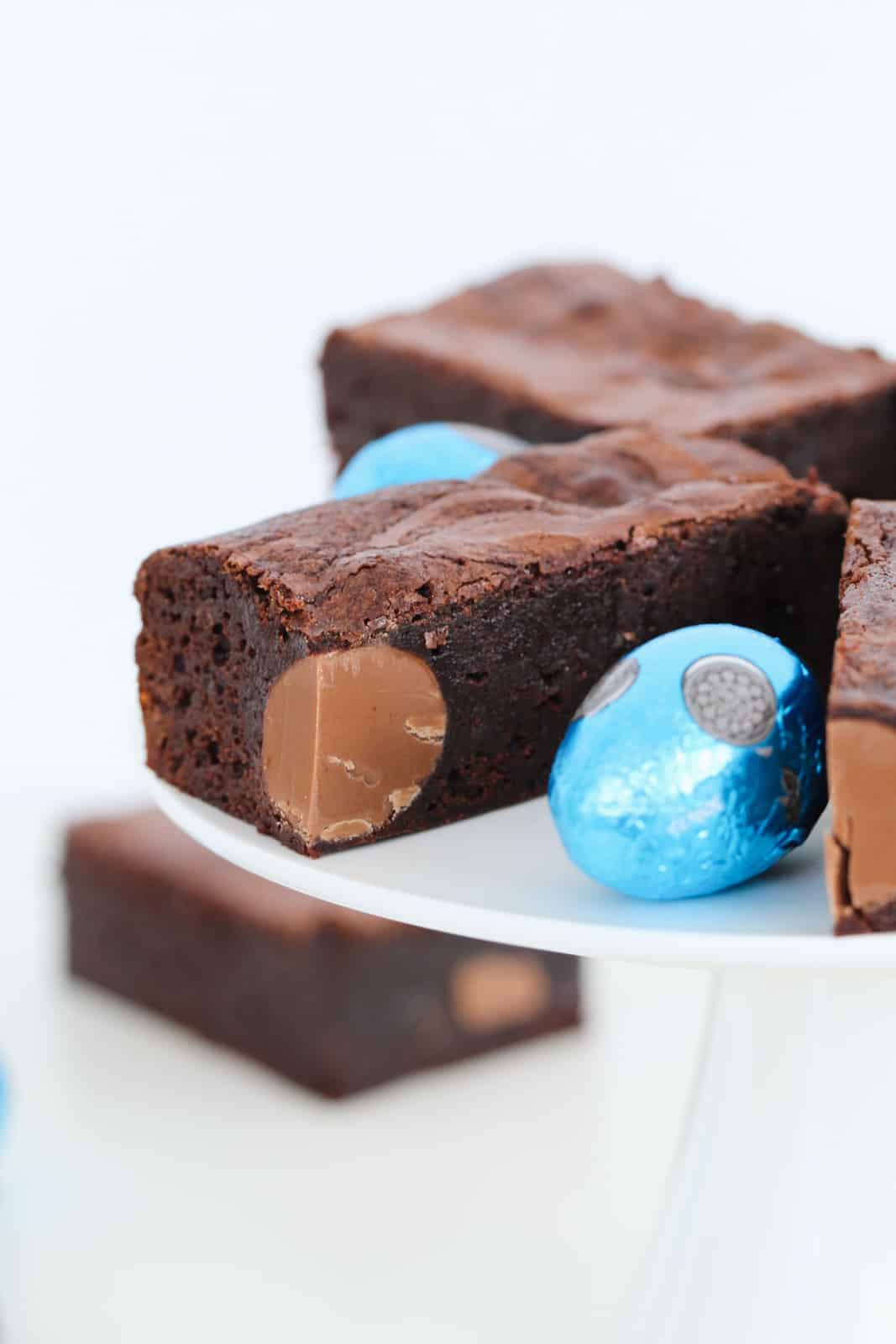 Pieces of Easter egg brownie slice on a white cake stand.