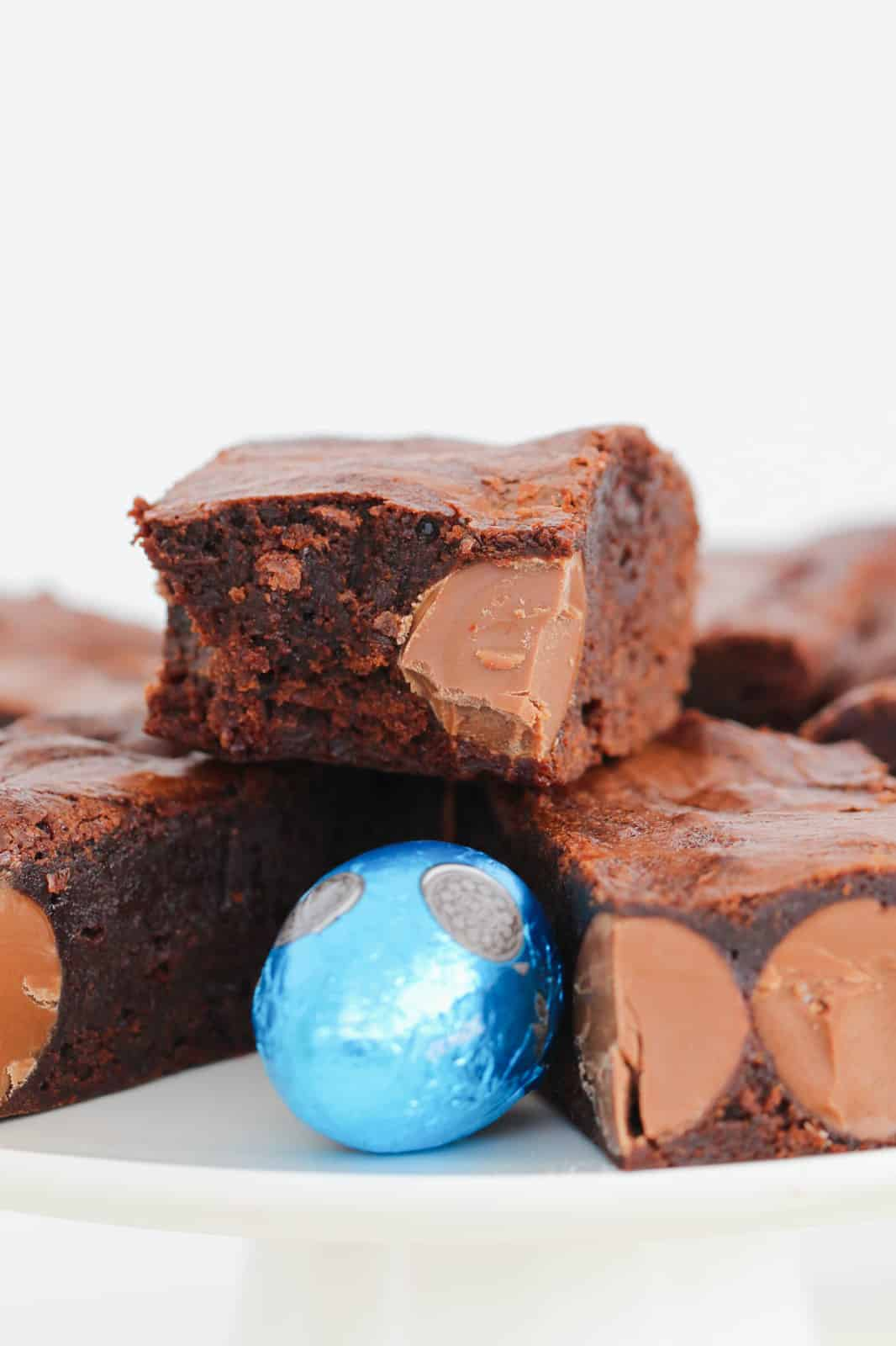 A half eaten square of Easter Brownie slice made with solid mini Easter eggs.