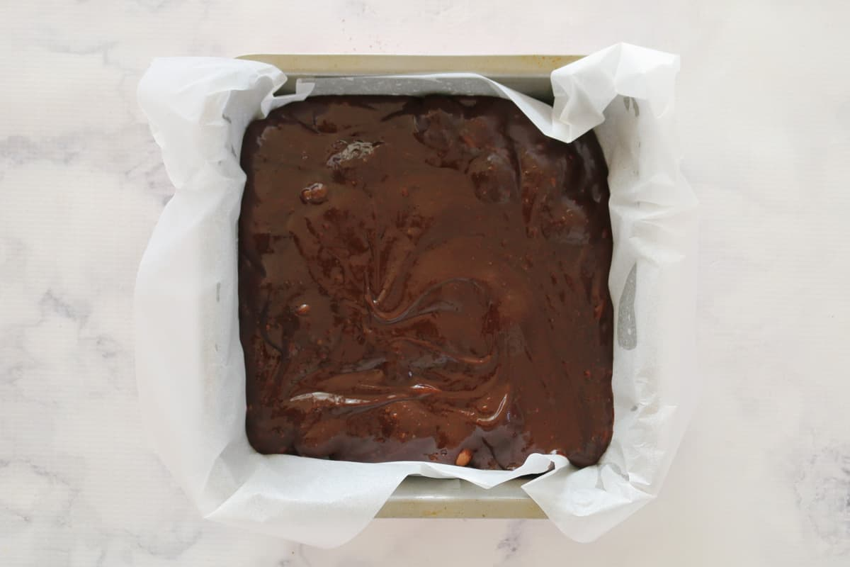 A square lined baking tin filled with chocolate brownie mixture.