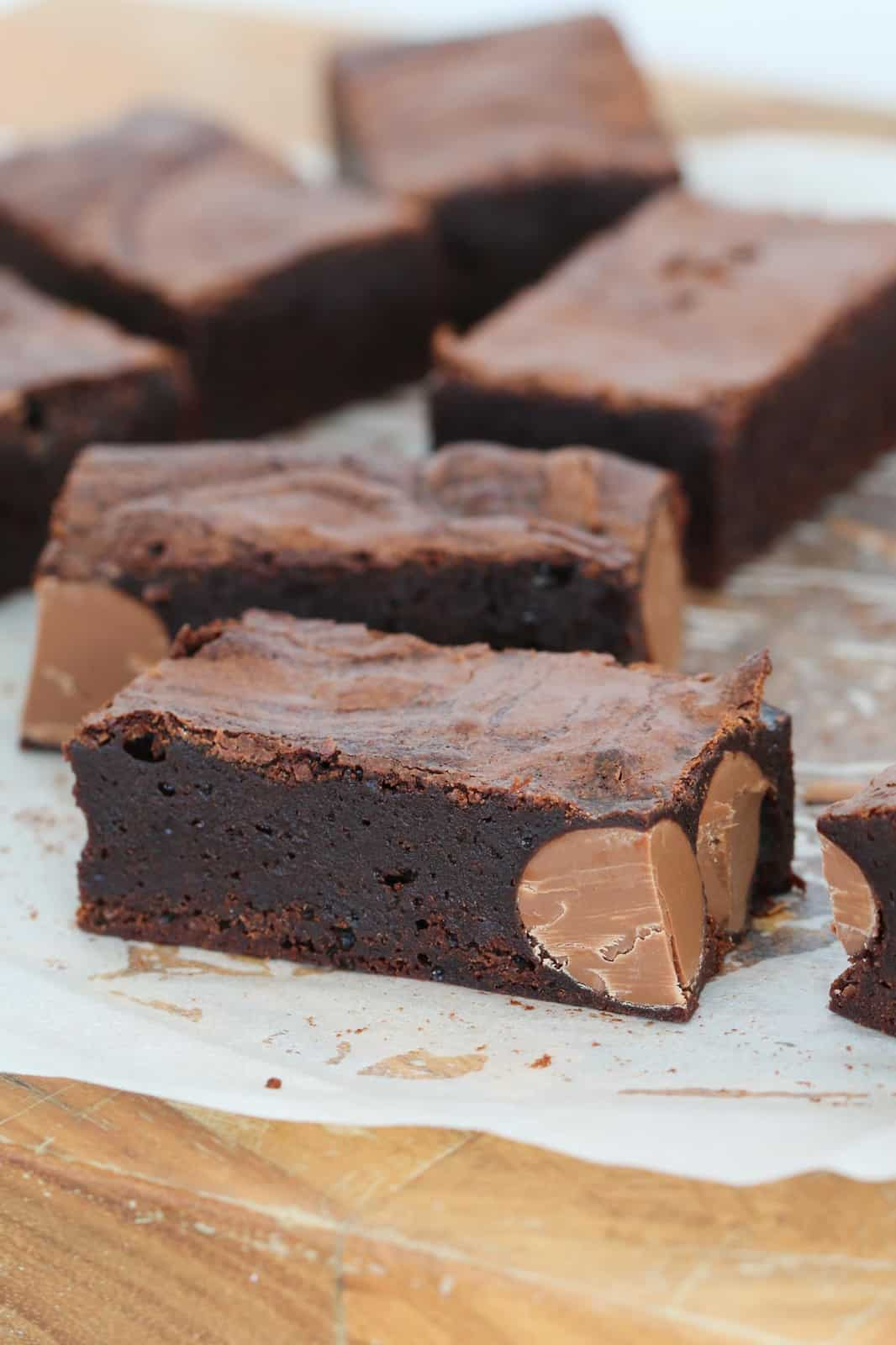 Slices of rich chocolate brownie with chocolate Easter eggs, on a chopping board.