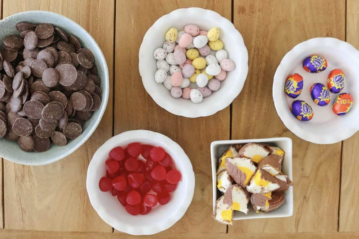 Chocolate, marshmallow eggs, Creme Eggs, lolly raspberries and mini speckled eggs on a board.