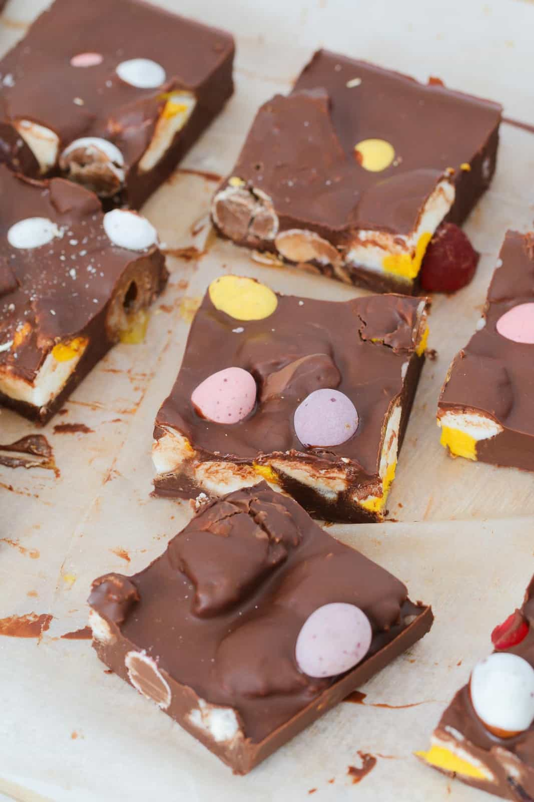 Baking paper with squares of Easter rocky road on top filled with Easter eggs and lollies.