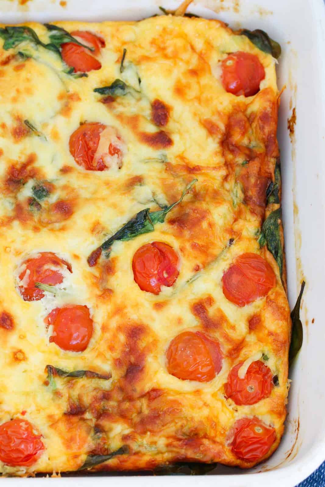 A baked egg frittata topped with cherry tomatoes and melted cheese.