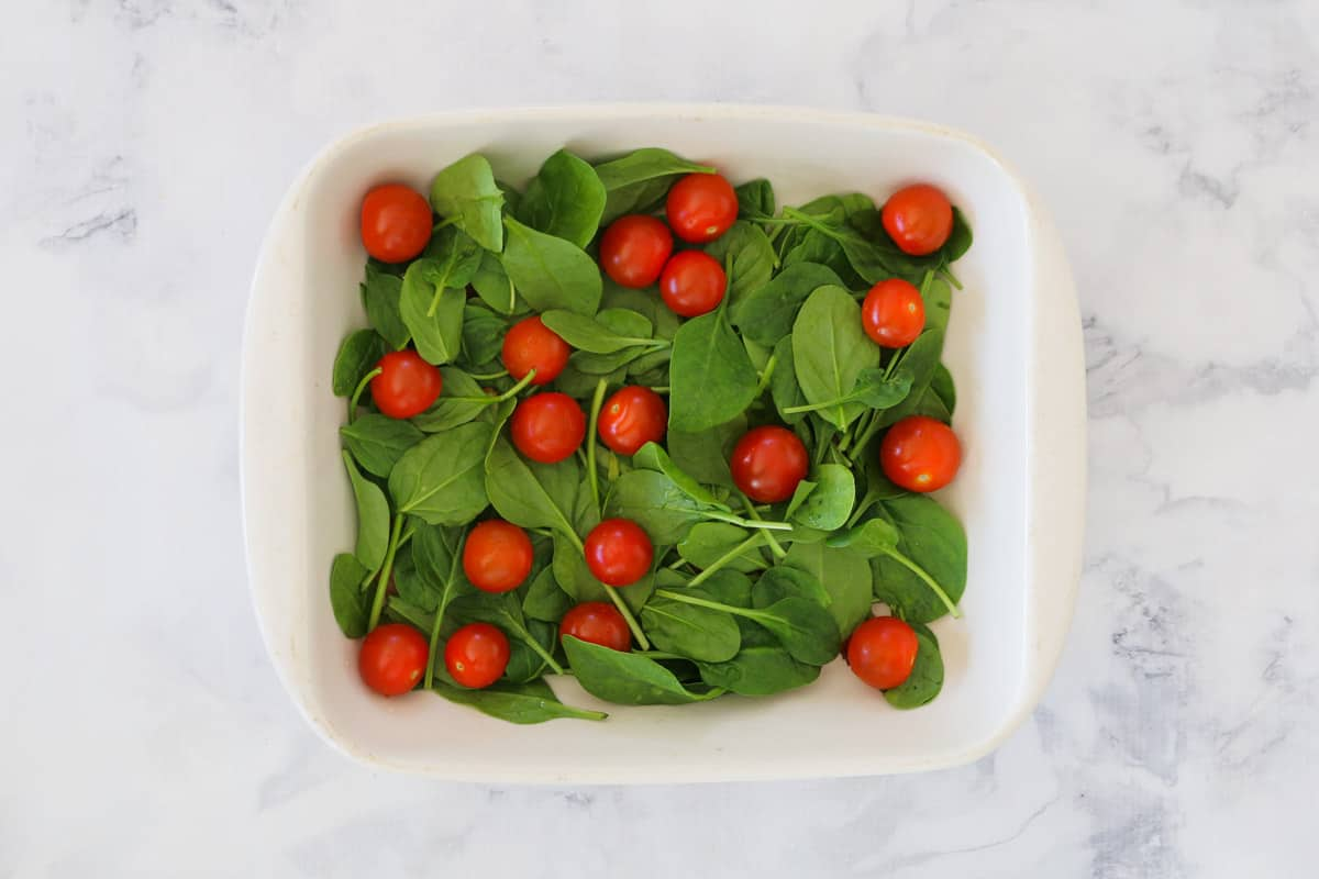 Spinach and tomatoes in a baking dish.