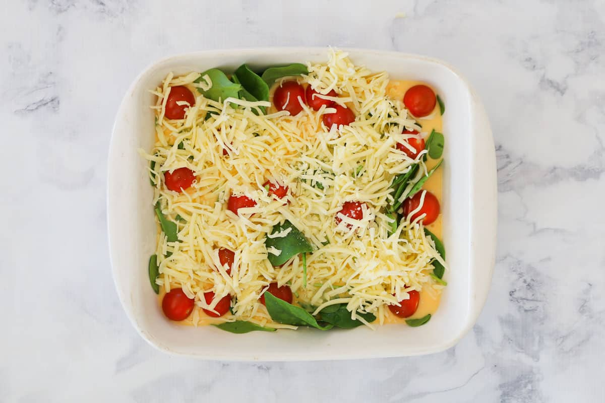 Grated cheese over an egg and vegetable mixture in a baking dish.