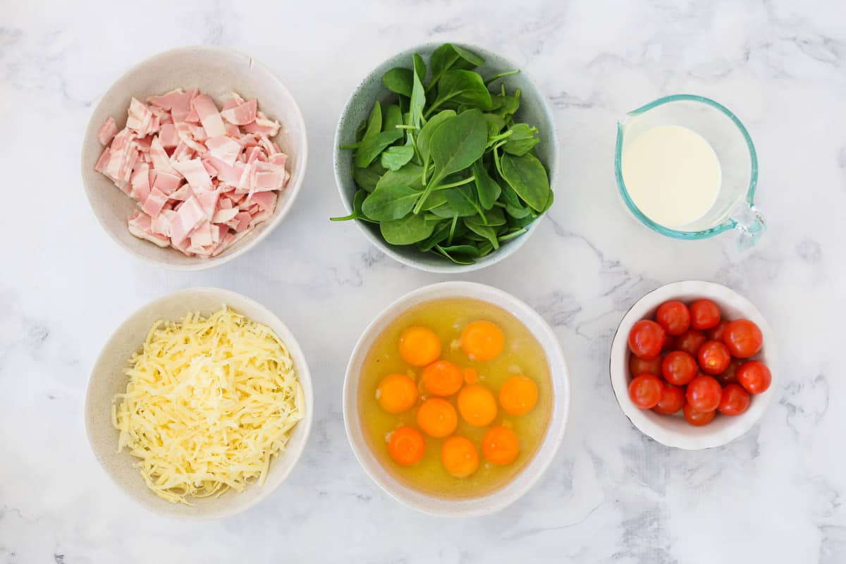 The ingredients for a spinach, tomato and bacon frittata.